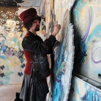Chris painting cut-out characters in front of the Narnia spray work mural at Leith Custom House, 2016.