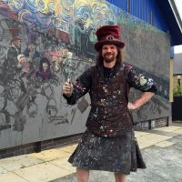 Chris wielding a paintbrush in front of the mural in Galashiels.
