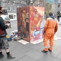 Artists Chris Rutterford and Elph assessing their work in the Grassmarket.
