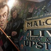 Hand-painted signage and Father Noel Furlong (Graham Norton) in the Father Ted mural on the staircase.